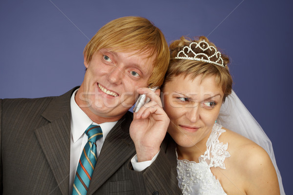 Groom calls on a cell phone, bride overhears Stock photo © pzaxe