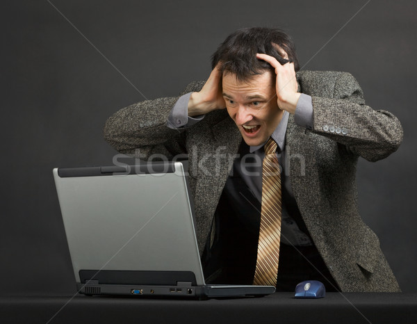 Нoung man shouts with despair looking at computer screen Stock photo © pzaxe