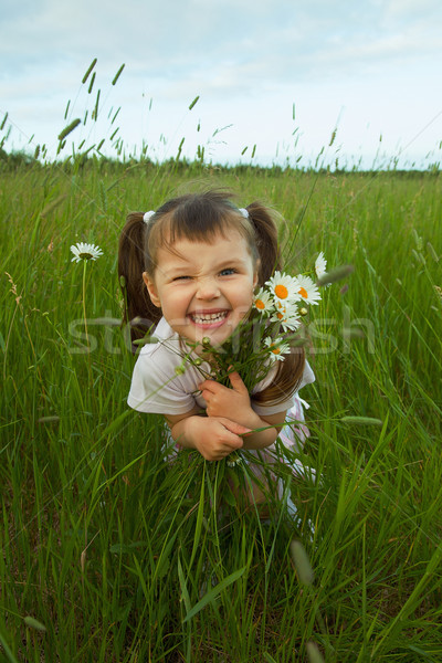 Cheerful child embraces wild flowers Stock photo © pzaxe