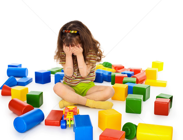 Little girl sitting on white among toys and crying Stock photo © pzaxe