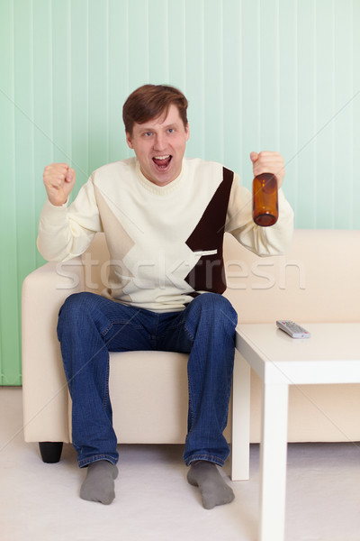Football fan sitting on sofa with TV Stock photo © pzaxe