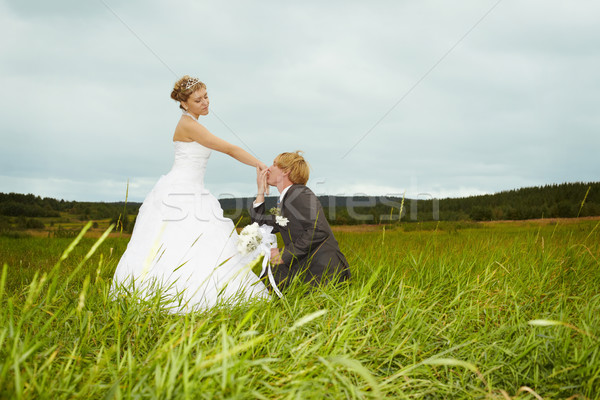Groom kisses hand of bride in field Stock photo © pzaxe