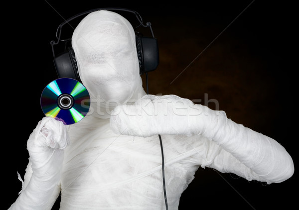 Stock photo: DJ costume mummy with ear-phones and disc