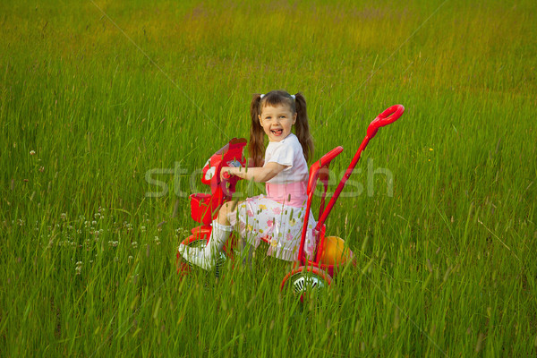 Little girl rides a bicycle on field Stock photo © pzaxe