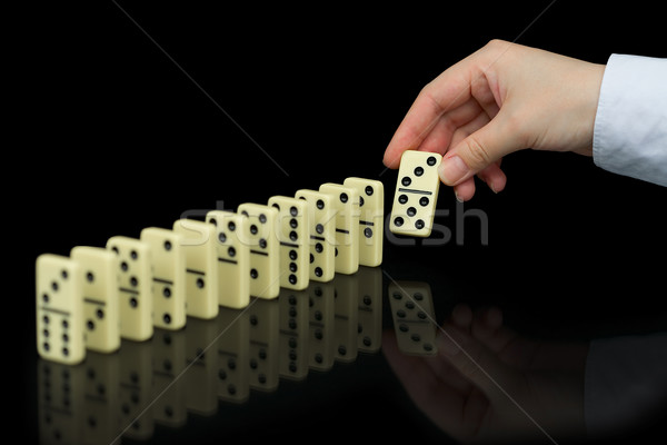 Hand builds a line of dominoes on black background Stock photo © pzaxe