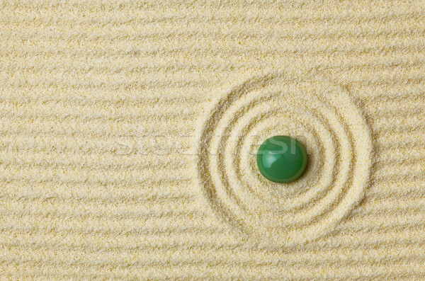 Green stone on surface of yellow sand Stock photo © pzaxe