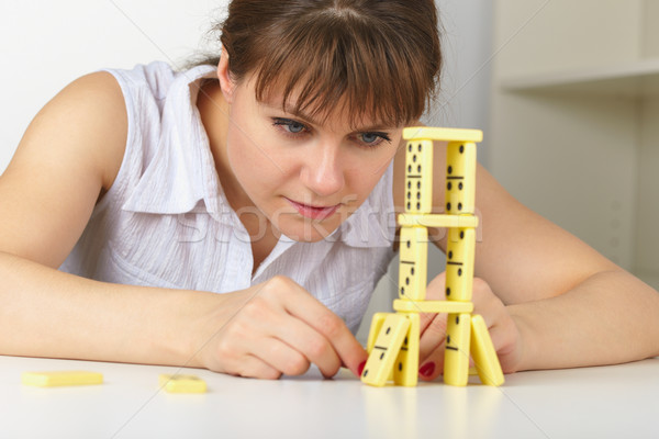 Young woman accurately builds tower of dominoes Stock photo © pzaxe