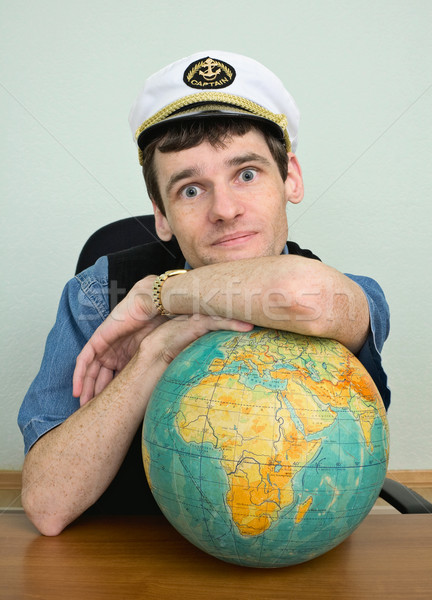Young man in a captain's cap with globe Stock photo © pzaxe