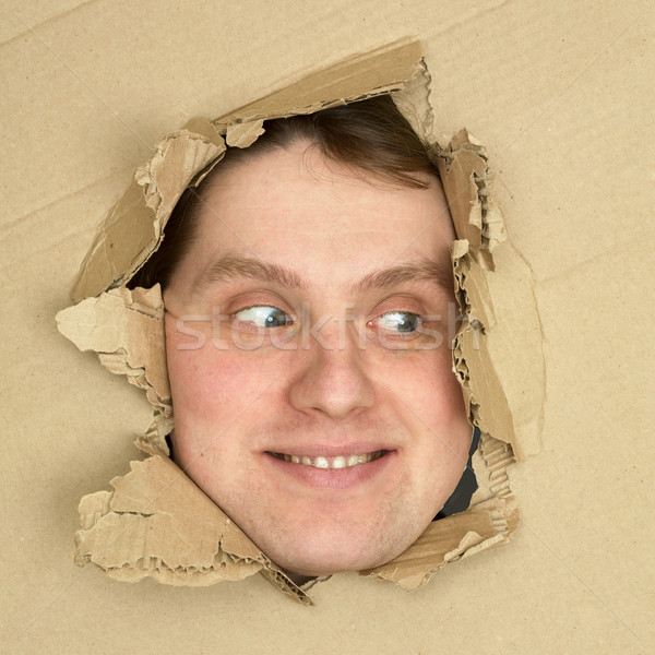 Male face look up from hole in carton Stock photo © pzaxe