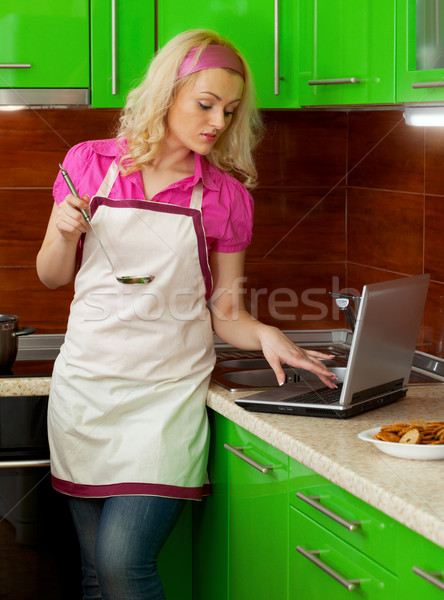 Beautiful young woman in the kitchen using a laptop Stock photo © pzaxe