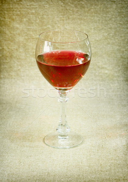 One glass with red wine against brown drapery Stock photo © pzaxe