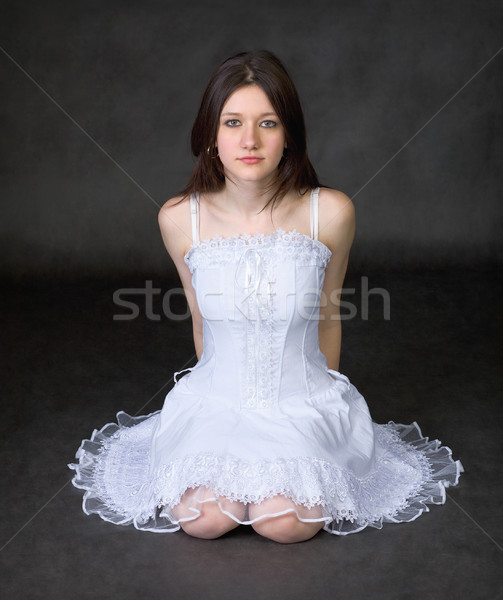 Girl in a white dress sits on a black background Stock photo © pzaxe