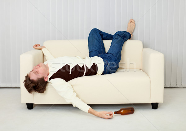 Drunkard sleeps on sofa in an amusing pose Stock photo © pzaxe