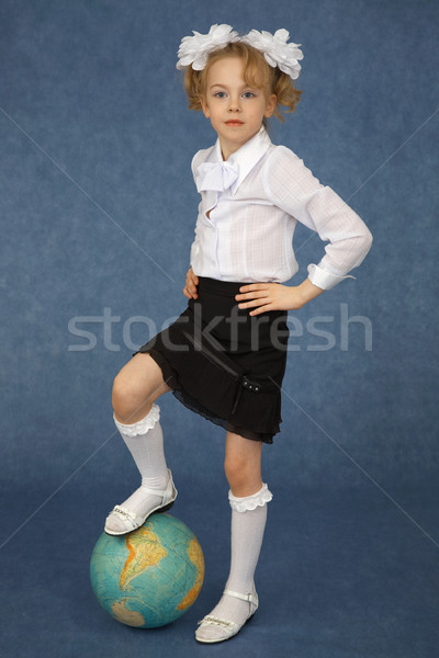 Schoolgirl put foot on globe Stock photo © pzaxe