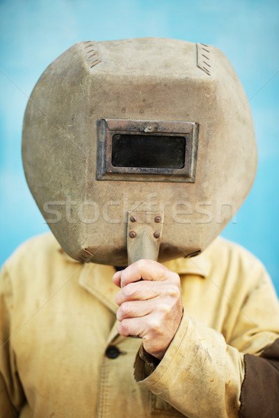 Old welder's helmet in hands of welder Stock photo © pzaxe