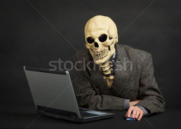 Terrible skeleton sits at black office with laptop Stock photo © pzaxe