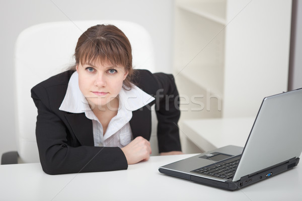 Resolutely woman - managing director sits at table with laptop Stock photo © pzaxe