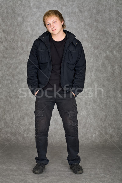 Young guy in a jacket standing on a grey background Stock photo © pzaxe