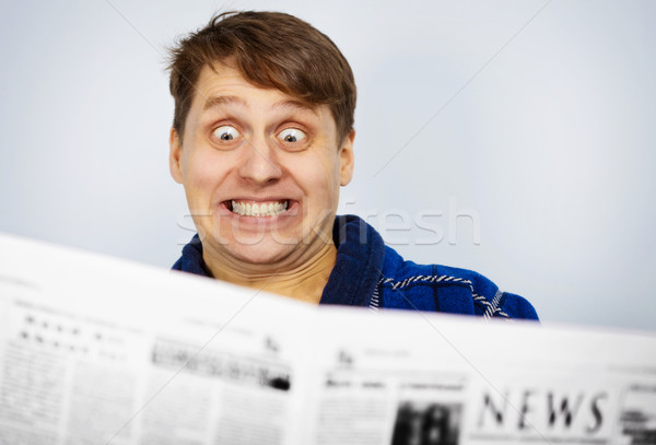 Stock photo: Man shocked by news from the newspaper