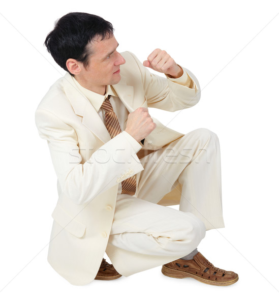 Businessman sitting in defensive posture Stock photo © pzaxe