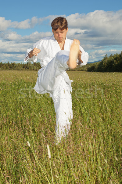 Jonge man witte kimono treinen slaan voet Stockfoto © pzaxe
