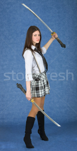 Girl with two swords on a blue background Stock photo © pzaxe