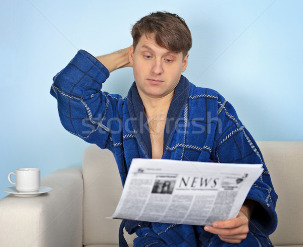 Person reads a newspaper with pensiveness Stock photo © pzaxe