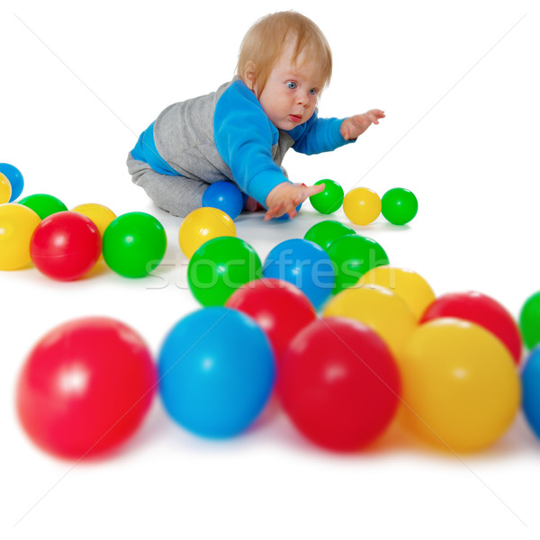 Comical child playing with colored plastic balls Stock photo © pzaxe