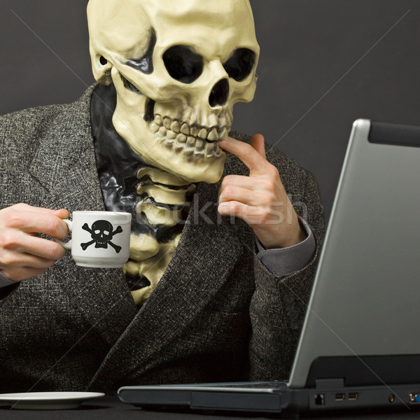 Skeleton drinks poisonous coffee at table with laptop Stock photo © pzaxe