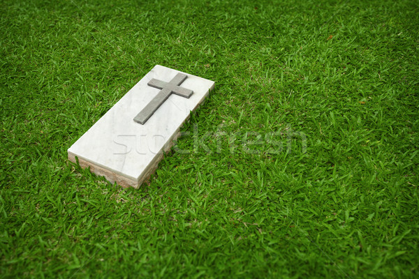 Marble tombstone with the Christian cross on a green lawn Stock photo © pzaxe