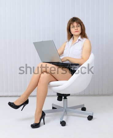 Young sexual girl - secretary sits in an armchair with laptop Stock photo © pzaxe