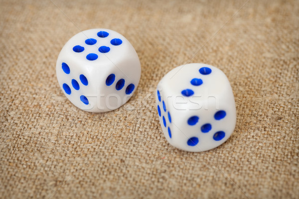 Two playing dices with blue points on brown canvas Stock photo © pzaxe