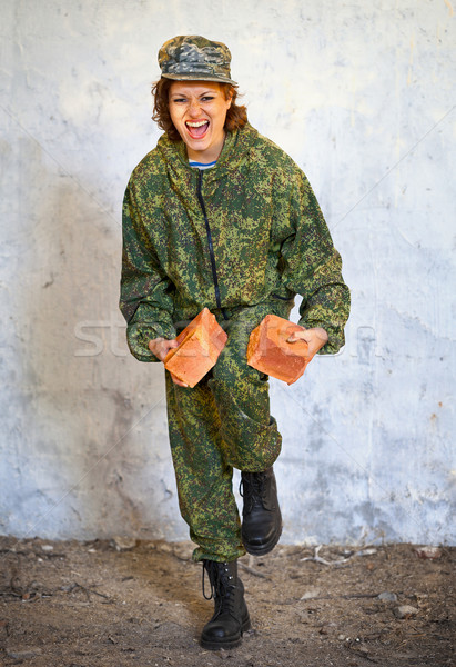 Woman from SWAT breaks brick with his knee Stock photo © pzaxe