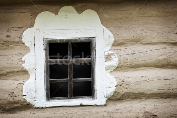 Window of ancient Ukrainian hut. Clay covered wall Stock photo © pzaxe