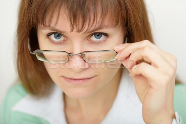 Young woman strictly looks over spectacles Stock photo © pzaxe