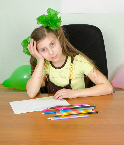 Girl sitting at a table with pencils Stock photo © pzaxe