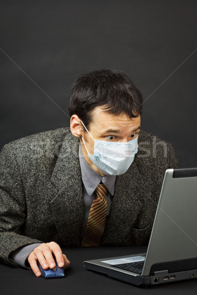 Surprised businessman in medical mask works in Internet Stock photo © pzaxe