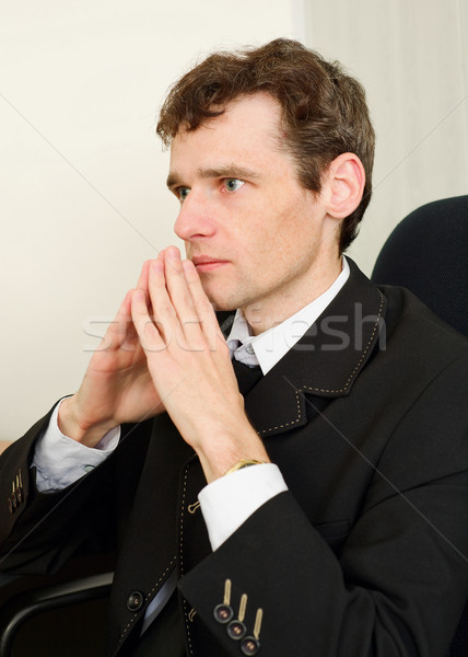 Guy in black jacket sits having combined hands Stock photo © pzaxe