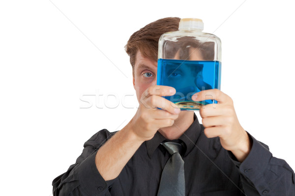 Stock photo: Man checks physical properties of liquid in bottle
