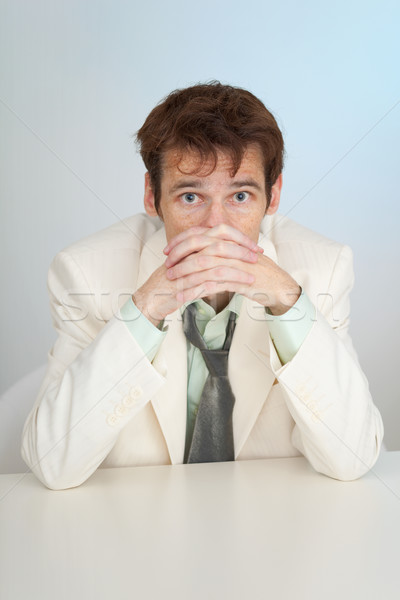 Young sorrowful person in white suit sits at table Stock photo © pzaxe