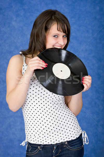 Girl biting a phonograph record on a blue Stock photo © pzaxe