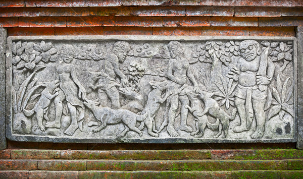 Stock photo: Images of people and dogs carved on a stone plate. Indonesia, Ba