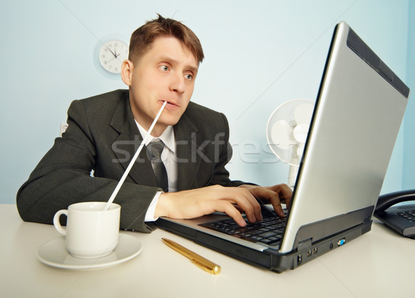 Businessman drinks coffee through a straw and work in Internet Stock photo © pzaxe
