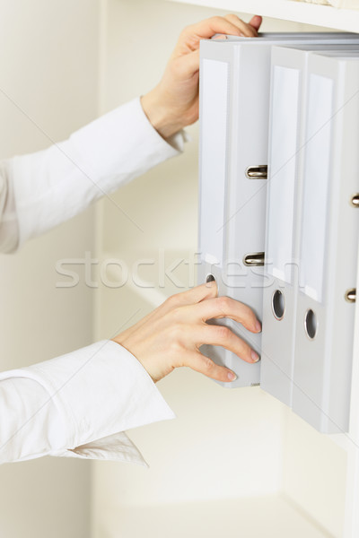 Hands of official remove from shelf a folder with classified doc Stock photo © pzaxe