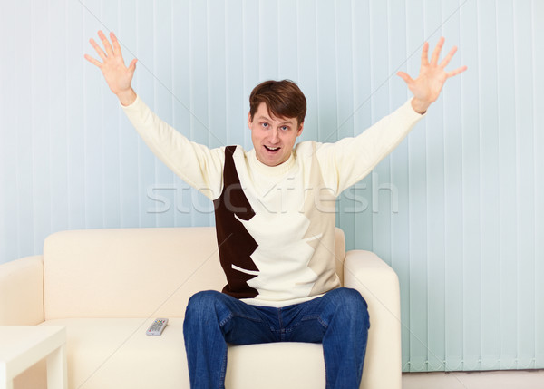 Young man exults sitting on sofa - sports fan Stock photo © pzaxe