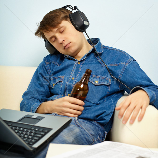 Stock photo: Man fell asleep at home on couch with a beer