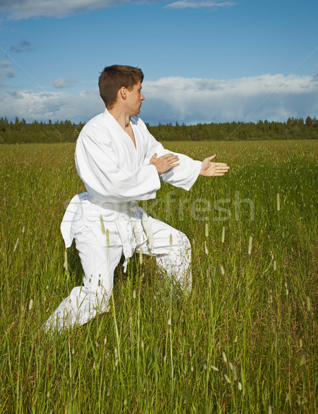 Нoung man goes in for karate in open air Stock photo © pzaxe
