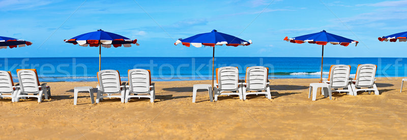 Sunbeds and umbrellas on a tropical beach Stock photo © pzaxe