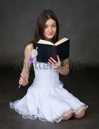 Girl - the magician with the book sits on black Stock photo © pzaxe