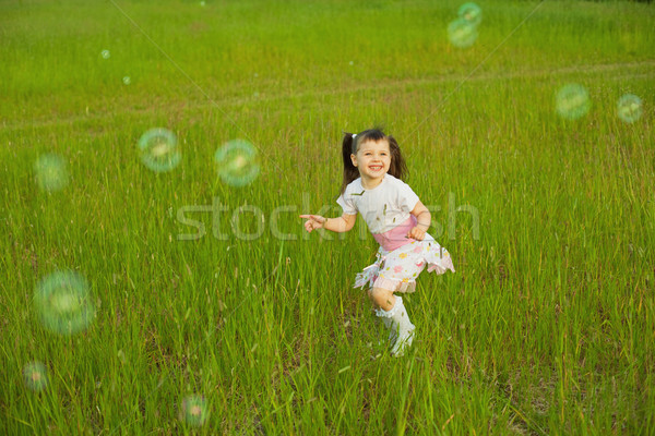 Happy little girl among soap bubbles Stock photo © pzaxe